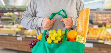 Customer hold reusable green shopping bag with fruit and vegetable over Supermarket aisle blur defocused product shelves interior bokeh light background