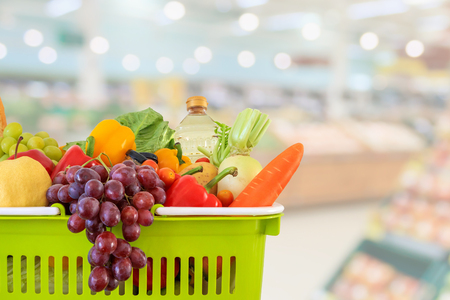 Shopping basket filled with fruits and vegetables with supermarket grocery store blurred defocused background with bokeh light