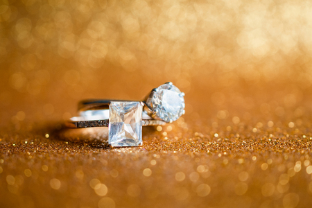 Jewelry diamond ring with abstract festive glitter Christmas holiday texture background blur with bokeh light Stock Photo