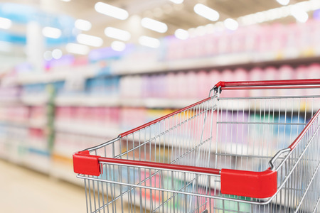 Empty red shopping cart with abstract blur supermarket discount store with body care cosmetic shelves interior defocused background 版權商用圖片