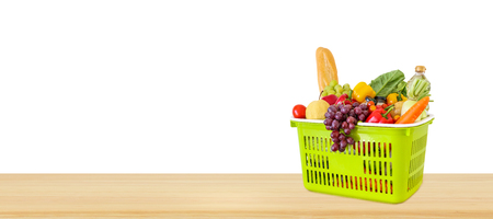 Fresh fruits and vegetables grocery product in green shopping basket on wood table top isolated on white background