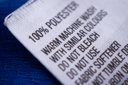 Polyester clothing label with laundry care instructions tag on blue shirt jersey Stockfoto
