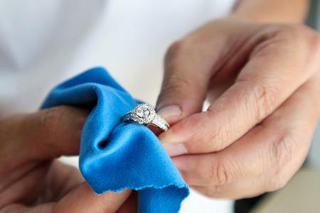 Juwelier met de hand polijsten en schoonmaken van sieraden diamanten ring met microvezelstof