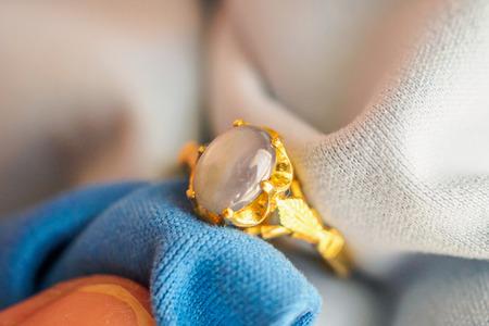 Jubiler ręcznie polerujący i czyszczący złoty pierścionek jubilerski z tkaniną z mikrowłókien