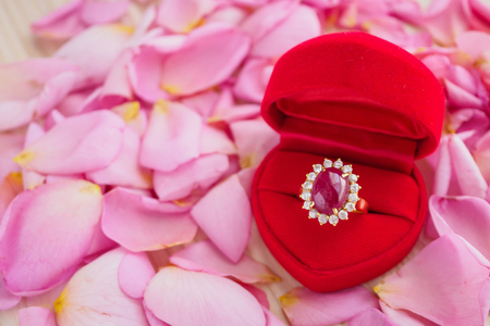 elegant ruby ring in red heart jewelry box on beautiful pink rose petal background close up