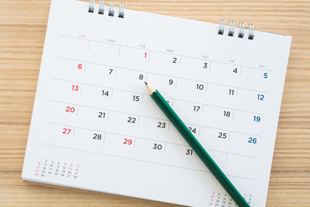 calendar page with pencil on wood table background