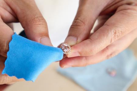 Bijoutier polissage à la main et nettoyage de bague en diamant de bijoux avec tissu en microfibre