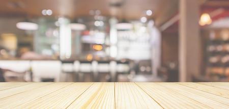 Dessus de table en bois avec intérieur de café-restaurant avec comptoir de bar flou abstrait avec lumière bokeh Banque d'images