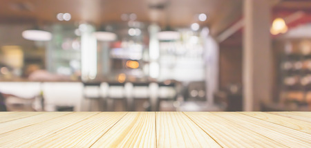 Holztischplatte mit Café-Restaurant-Interieur mit Bartheke verwischen abstrakten Hintergrund mit Bokeh-Licht Standard-Bild