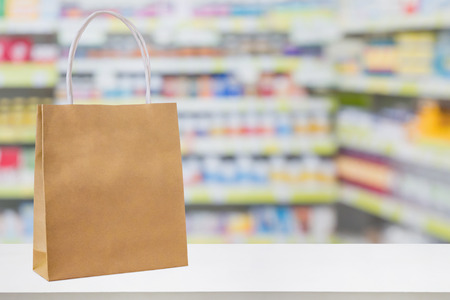 Paper bag on Pharmacy drugstore counter table with medicine and healthcare product on shelves blur background