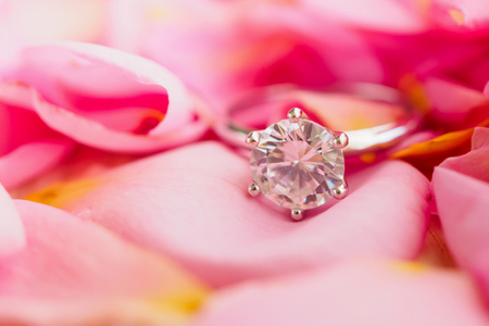 Jewelry diamond ring on beautiful pink rose petal background close up Banque d'images