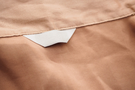 blank white clothing label on brown fabric texture background 스톡 콘텐츠
