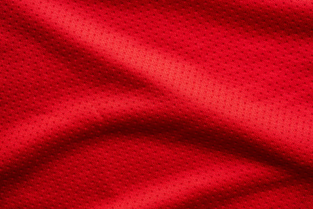 Red fabric sport clothing football jersey with air mesh texture background Фото со стока