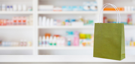 Paper bag on Pharmacy drugstore counter table with medicine and healthcare product on shelves blur background 免版税图像