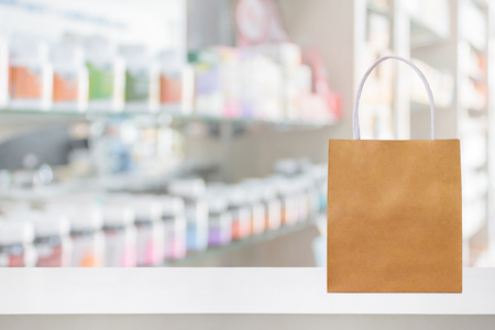 Paper bag on Pharmacy drugstore counter table with medicine and healthcare product on shelves blur background Imagens