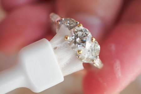 Jeweller hand cleaning and polishing vintage jewelry diamond ring closeup macro 版權商用圖片