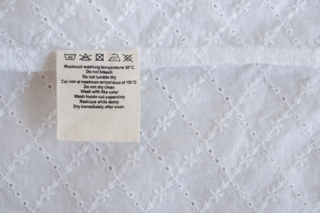 laundry care washing instructions clothes label on fabric texture background