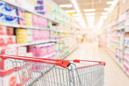 Empty shopping cart with abstract blur supermarket discount store aisle and toilet tissue paper display product shelves interior defocused background