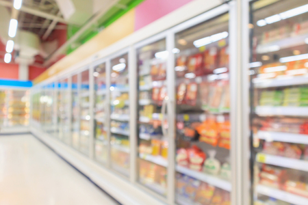 supermarket aisle with commercial refrigerators freezer showing frozen foods abstract blur background