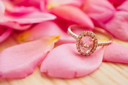 Jewelry pink diamond ring on wood table with beautiful rose petal background close up