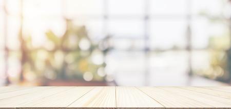 Leere Holztischplatte mit Café-Restaurant-Kaffee-Schaufenster-Innenraum abstrakte Unschärfe defokussiert mit Bokeh-Lichthintergrund für Montage-Produktanzeige Standard-Bild