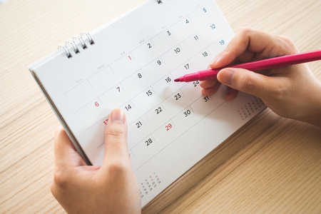 Hand with pen writing on calendar page closeup