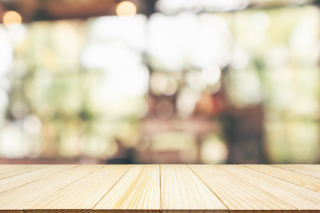 Empty wooden table top with cafe restaurant or coffee shop window interior abstract blur defocused with bokeh light background for montage product display