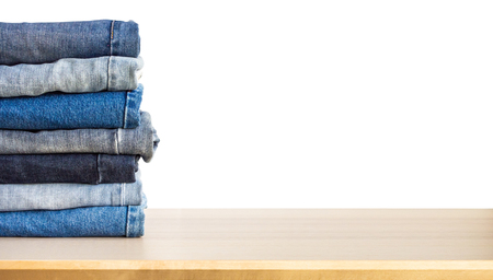 denim blue jeans stack on wood table isolated on white background
