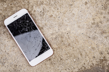 broken glass of mobile phone screen on concrete floor background