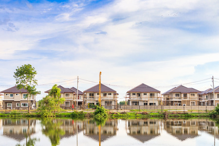 New house building reflection with water in lake at residential estate construction site with clouds and blue sky Banco de Imagens - 124855542