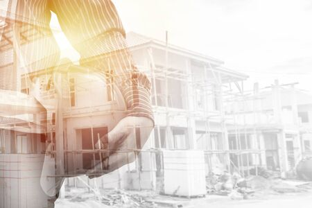 Construction engineer worker hold helmet double exposure with residential new house in progress at building site