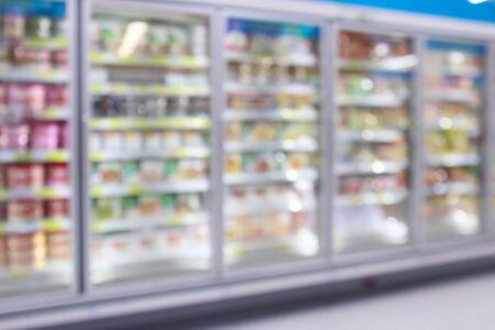 Gefrierschrank für gewerbliche Kühlschränke im Supermarkt, der den Hintergrund der abstrakten Unschärfe von Tiefkühlkost zeigt