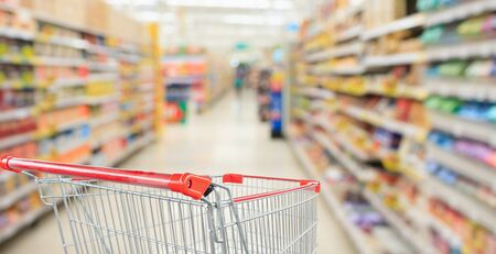 Supermarket aisle blurred background with empty red shopping cart