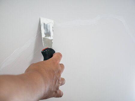 Plasterer hand repair crack white wall