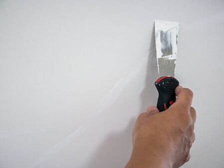 Plasterer hand repair crack white wall