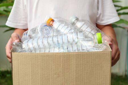 Mano que sostiene la caja de basura de reciclaje marrón con botellas de plástico Foto de archivo