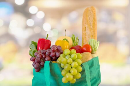 Fresh fruits and vegetables in reusable green shopping bag with supermarket grocery store blurred defocused background with bokeh light Stockfoto
