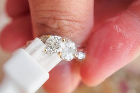 Jeweller hand cleaning and polishing vintage jewelry diamond ring closeup macro Foto de archivo