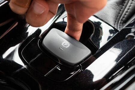 Hand push on electronic handbrake button in luxury modern car