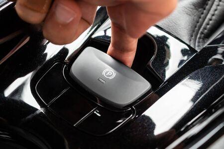 Spingere a mano il pulsante del freno a mano elettronico in un'auto moderna di lusso Archivio Fotografico