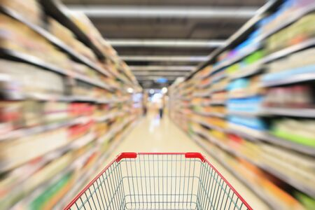 Red Shopping cart view with supermarket aisle shelves interior abstract blur defocused background
