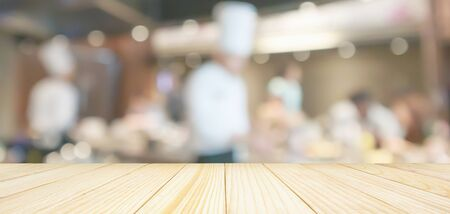 Empty wood table top with chef cooking in restaurant kitchen blurred defocused background Zdjęcie Seryjne