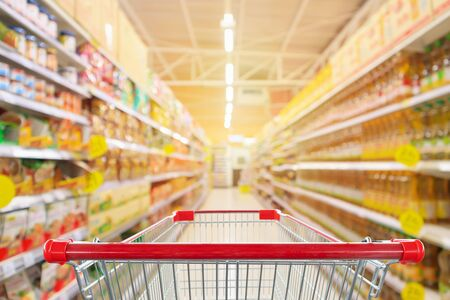 Empty red shopping cart with supermarket aisle with seasoning and cooking vegetable oil bottles product shelves interior defocused blur background