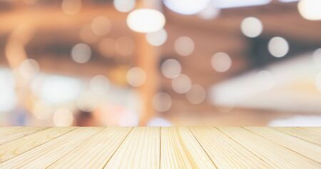 Empty wood table top with cafe restaurant with abstract bokeh lights defocused blur background