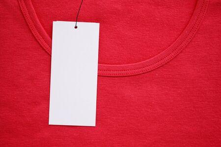 Blank white clothes tag label on new red shirt Zdjęcie Seryjne