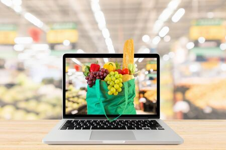 supermarket aisle blurred background with laptop computer and green shopping bag on wood table grocery online concept 版權商用圖片