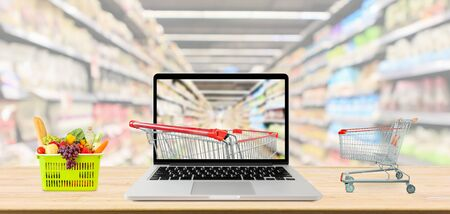supermarket aisle blurred background with laptop computer and shopping cart on wood table grocery online concept