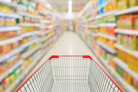 supermarket aisle with empty shopping cart and product shelves interior defocused blur background 版權商用圖片