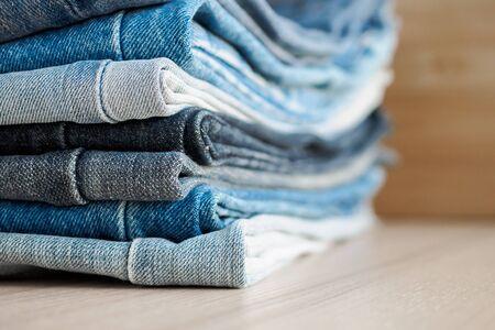 pile de jeans bleu denim sur fond de table en bois