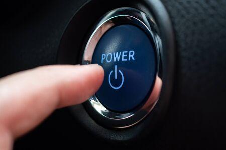 Hand push on car engine power start button close up